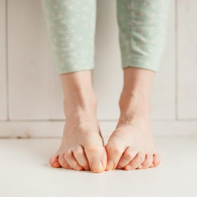 Women's tired ankles with clasped fingers and bulging veins close-up on a light background
